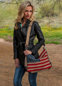 Suede flag handbag with studded stars and leather trim. Large main compartment with top zip closure. Interior zip pocket and organizing pockets. Removable and adjustable cross body leather shoulder strap.